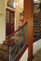 Fluted mahogany column, mahogany handrail, ornamental ironwork and matching doors were designed and built for a remodel of existing steps.