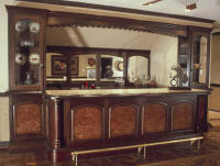 This 14-ft. mahogany bar and back bar include granite tops, Carpathian elm burl veneers on panels and columns with gold leaf.  The work was distressed and glazed to give the effect of a Victorian period piece.