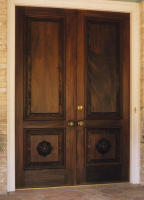 Massive carved mahogany doors in this entryway featuring deeply carved rosettes on the lower panels.