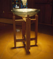 A stained oak baptismal font for an Episcopal School Chapel matching the design of the altar and lectern built by Landers Studio.